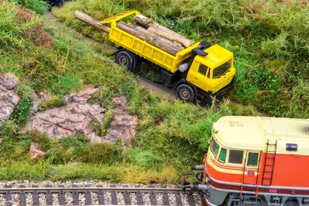 Yellow truck on model train railroad layout in H0 scale with wood near locomotive Stock Photo - 149337054