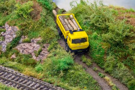 Yellow truck on model train railroad layout in H0 scale with wood ride down from hill Stock Photo - 149338131