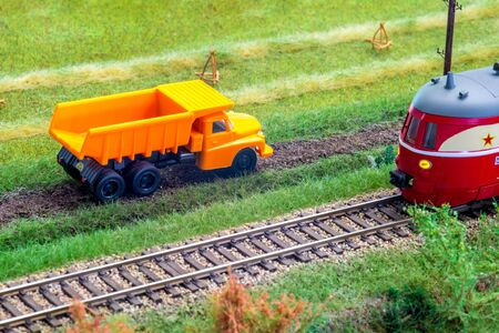Orange truck on model train layout pass by passenger train Stock Photo - 149337257