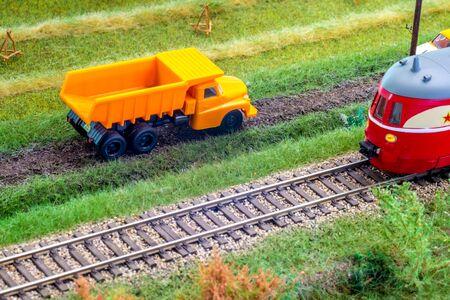 Orange truck on model train layout pass by passenger train Stock Photo - 149336750