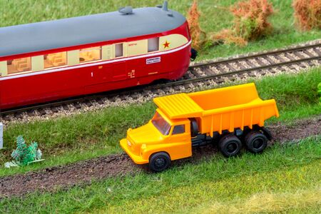 Orange truck on model train layout next to historic passenger train Stock Photo - 149337587