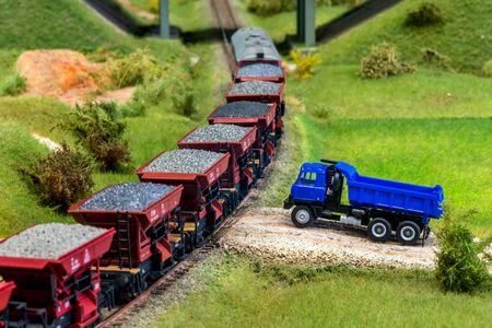 Model train cars loaded by coal with heavy truck, model scale H0 Stock Photo - 149336822