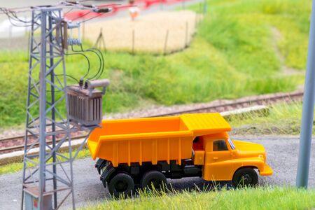 Orange truck in H0 scale on model train road Stock Photo