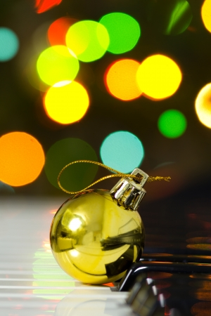 Christmas decoration ball on a piano against defocused lights background photo