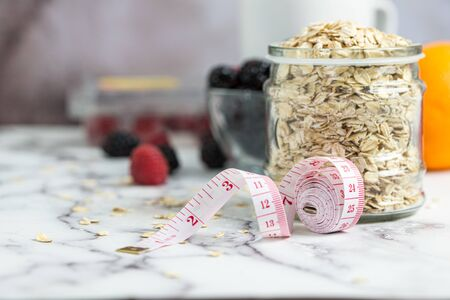 Measuring tape, oats and fresh berries for healthy slimming diet concept Reklamní fotografie