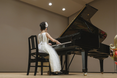 Het meisje dat de piano speelt op het podium Stockfoto
