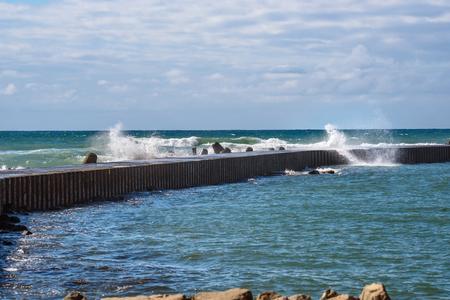 De golven verslaan de golfbreker Stockfoto - 85355033