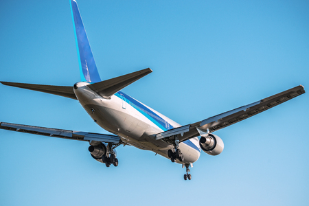 The passenger plane which flies in the blue sky Stock Photo