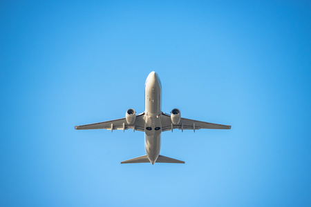 The passenger plane which flies in the blue sky Imagens