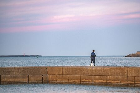 Beautiful sunset and angler at breakwater