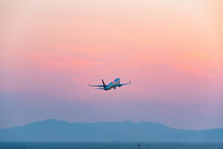 The passenger plane which takes off for the sunset sky 版權商用圖片