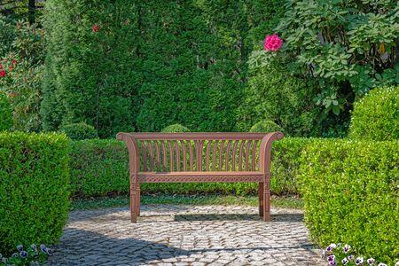 Wooden bench in the beautiful garden 写真素材