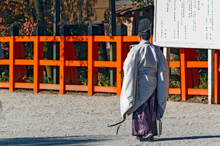 A shinto priest walking along the shrine approach