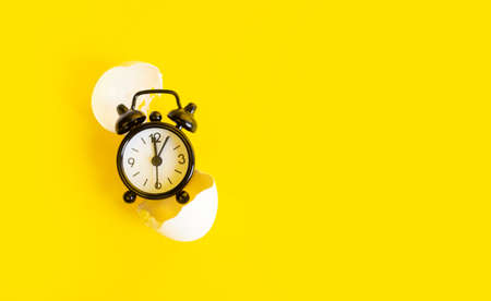 Black clock on a yellow background