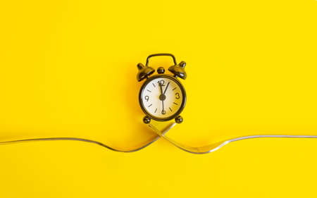 Black clock on a yellow background. Alarm clock on two forks, trend concept time .