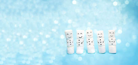Snowmen on a blue background with bokeh effect. Banner for the website header. Christmas holiday concept.