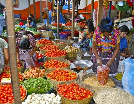 女性はカラフルなグアテマラの市場での労働者を生成します。 報道画像