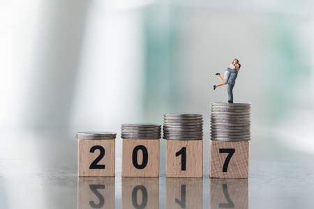 top 7: 2017 year and love and family concept. Couple in love of man and woman stand on top of stack of coins on 2 0 1 7 number wooden blocks. Stock Photo
