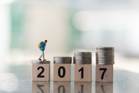 Travel and Planing concepts. Traveler miniature mini figures with backpack walking on top of stack of coins on top of  2 0 1 7 number wooden block