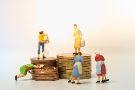 Money and saving concept. Group of women cleaner washing and cleaning coins in stack of coins Stock Photo