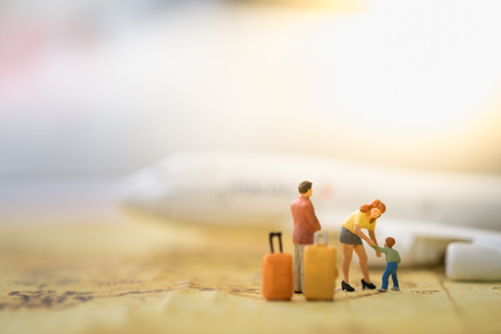 small world: Family and travel concept. Father, mother and son miniature figures with luggages standing, playing and take care child on world map with airplane model as background.