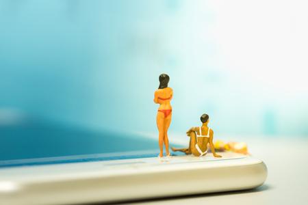 Sport en technologie concept. Groep vrouwen die zwempak dragen die bevinden zich, die en op het slimme telefoonscherm zitten leggen.