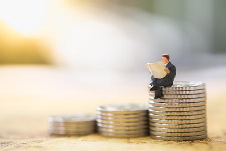Finanza, affari, concetto di risparmio. Chiuda su del giocattolo miniatura della figura dell'uomo d'affari che si siede e che legge un giornale sopra la pila di monete Archivio Fotografico