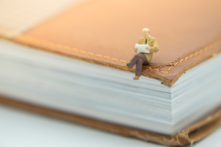 Reading and hobby concept. Miniature mini figures male sitting on a big book and reading a book. Stock Photo