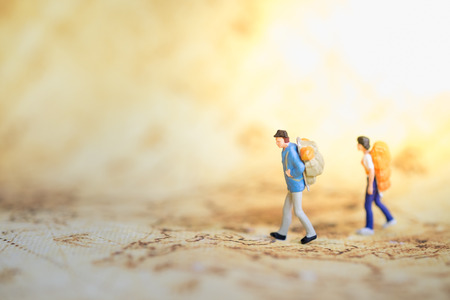 Two traveler miniature people figures with backpack standing and walking on world map. Travel and Journey concept.