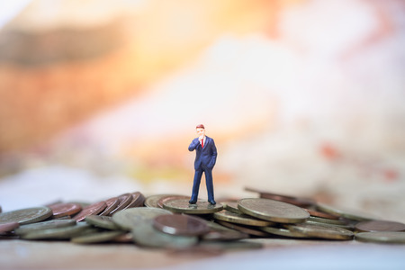 Money, Financial, Business Growth concept, Businessman miniature figures stand and thinking to business plan on top of pile of coins