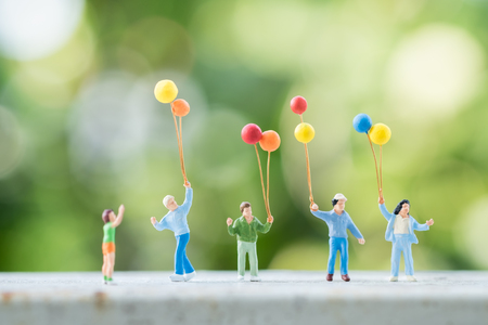 Family day and Kid Concept. Group of children miniature people figures with colorful balloon with green nature background. Stock Photo