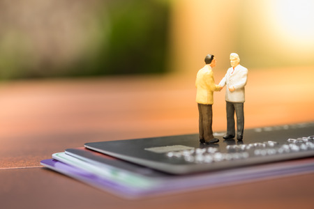 technology transaction: Business, finance and eCommerce concept. Two businessman miniature people figures hand shake and meeting on stack of credit cards. Stock Photo