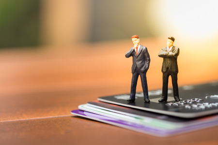 technology transaction: Business, finance and eCommerce concept. Two businessman miniature people figures standing, thinking and planning on stack of credit cards. Stock Photo