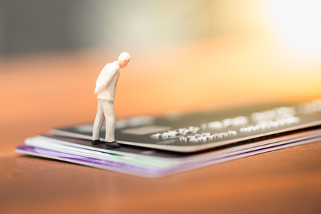 Business, finance and eCommerce concept. Businessman miniature people figures walking on stack of credit cards. Stock Photo