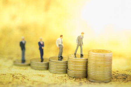 Money, Financial, Business Growth concept, Group of businessman miniature figures standing and walking to the top of stack of coins.