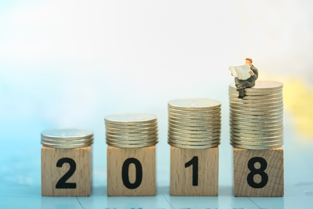 2018 New year and Business concept. Busnessman miniature people figure sitting and reading newspaper on stack of coins on number wooden blocks toy on world map.
