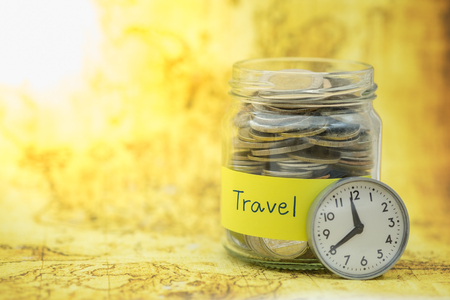 Time, Travel and Saving Concept. Full of coins in clear bottle with yellow label note with Travel word and vintage round watch on wolrd map.