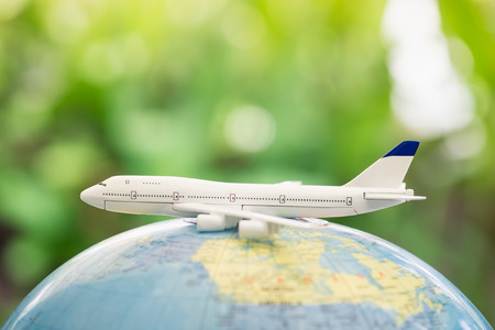 small world: Travel and transport concept. Toy airplane on world map balloon with green nature as background. Stock Photo