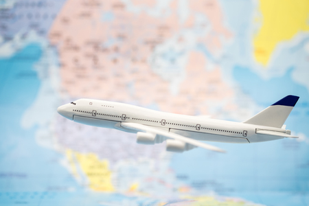 Travel and Transport concept. Close up of airplane toy with world map as background