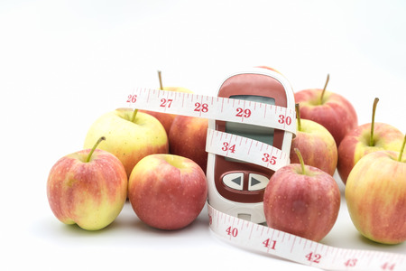 Medicine, diabetes, glycemia, health care, food and people concept - close up of Glucose meter with tape measure and apples.
