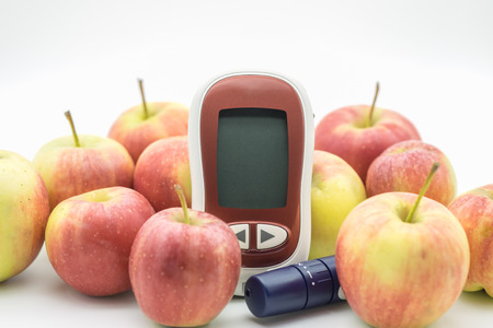 Medicine, diabetes, glycemia, health care and people concept - close up of Glucose meter and lancet for check blood sugar level with fresh apples.