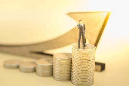 Concetto di denaro, affari, risparmio e crescita. Chiuda su della figura miniatura dell'uomo d'affari che sta e che pensa sopra la pila di monete d'argento con il simbolo di legno della freccia.