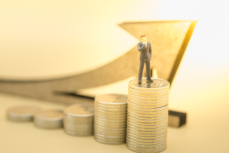 Money, business, saving and growth concept. Close up of businessman miniature figure standing and thinking on top of stack of silver coins with wooden arrow symbol.