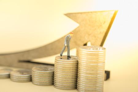 Geld, zaken, sparen en groeiconcept. Sluit omhoog van zakenman miniatuurcijfer die bovenop stapel zilveren muntstukken met houten pijlsymbool lopen. Stockfoto