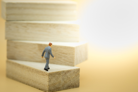 Business, growth and Succession concept. Businessman miniature figure walking to the top on wood stair made from wooden blocks toy. Stock Photo