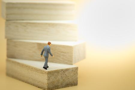 Concepto de negocio, crecimiento y sucesión. Empresario miniatura figura caminando hacia la cima en la escalera de madera hecha de bloques de madera de juguete.