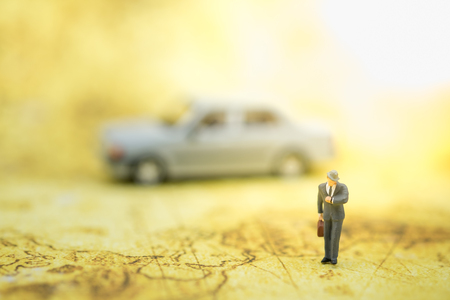 Business and Travel Concept. Businessman miniature figure with handbag looking to time on his watch on wrist with mini car model on behind and world map as background.