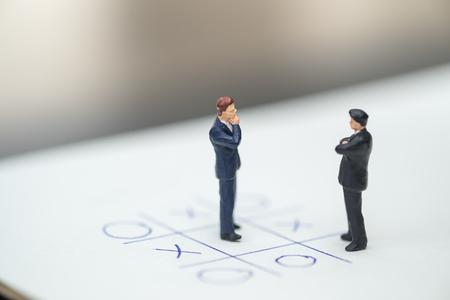 Dirección de negocios y concepto de planificación. Figura en miniatura de dos hombres de negocios de pie, cara a cara y pensando en papel con el juego de mesa OX (tic tac toe). Foto de archivo