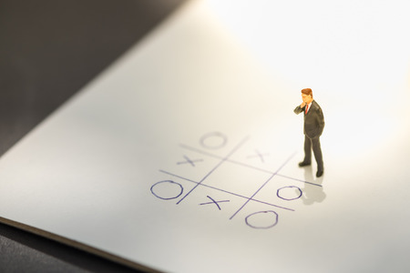 Business direction and planning concept. Businessman miniature figure standing and thinking on paper with OX (tic tac toe) board game. Banco de Imagens