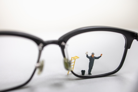 Cerca de la figura en miniatura del trabajador masculino limpie y limpie unas gafas de lectura sucias con un cubo y una escalera.